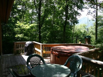 Enjoy the hot tub and mountain view in a wooded setting